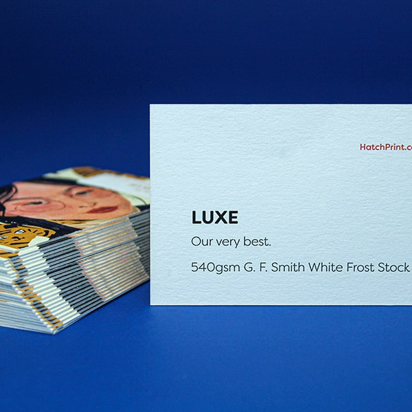 2 white business cards out-lined in blue. The left card contains a square in the upper left and copy 'Name here, Job title here' on the right. The other card contains a large upward facing arrow within a circle. It represents the first step when ordering with Hatch: select your product.