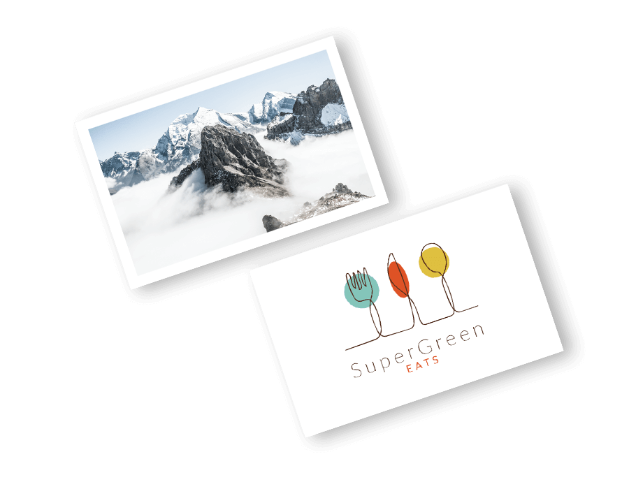Example white business card featuring image of mountains, and another white business card with stylised green, red and yellow cutlery with 'SuperGreen, Eats' text in black text. Some of the design options for you to stand out with a beautiful business card.
